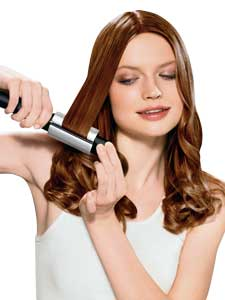 This is a picture of a woman using the curning iron