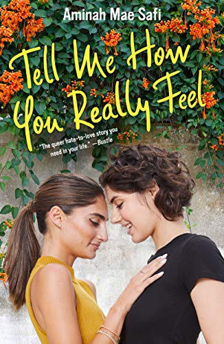 Tell Me How You Really Feel by Aminah Mae Safi. Two teen girls are standing close together in front of a wall covered in ivy and flowers. They're looking at each other and smiling.